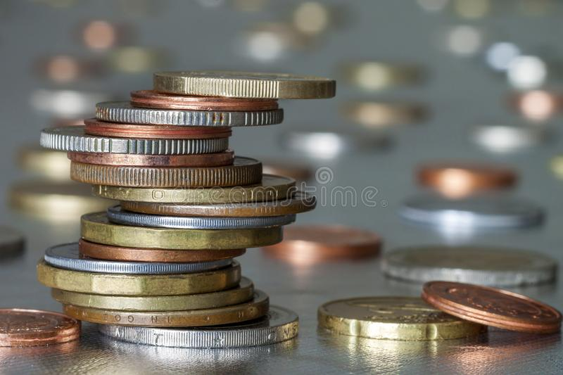 Pile of shiny coins different sizes and colors stacked unevenly on each other on colorful blurred blue abstract background. Money stock photos