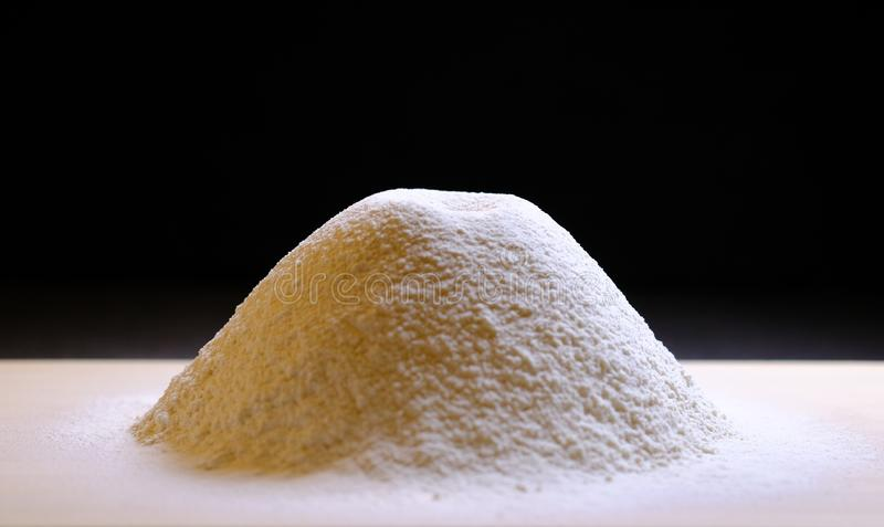 A pile of sifted flour on the kitchen table. Black background stock image