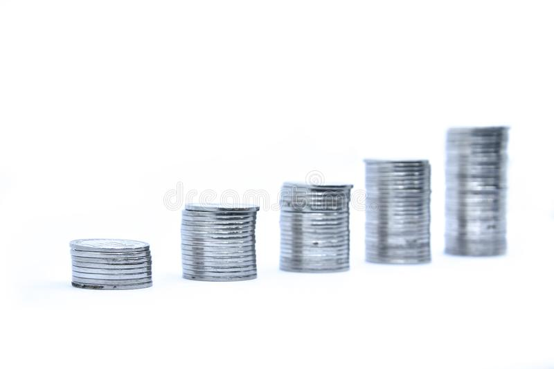 Pile of silver coins stack and growing money graph on rows, isolated on white background with clip path. Income, profits, finance, stock photography
