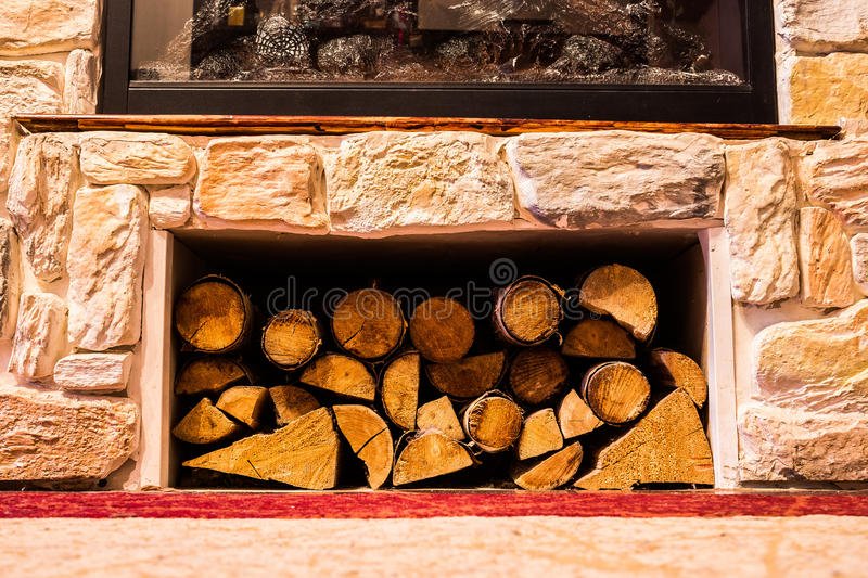 Pile of small logs under a fireplace stock image