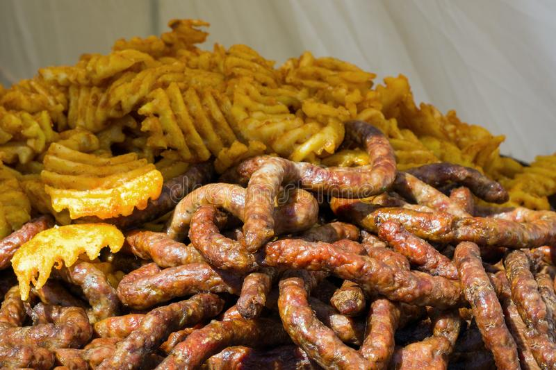 A pile of smoked sausages and potato chips stock image
