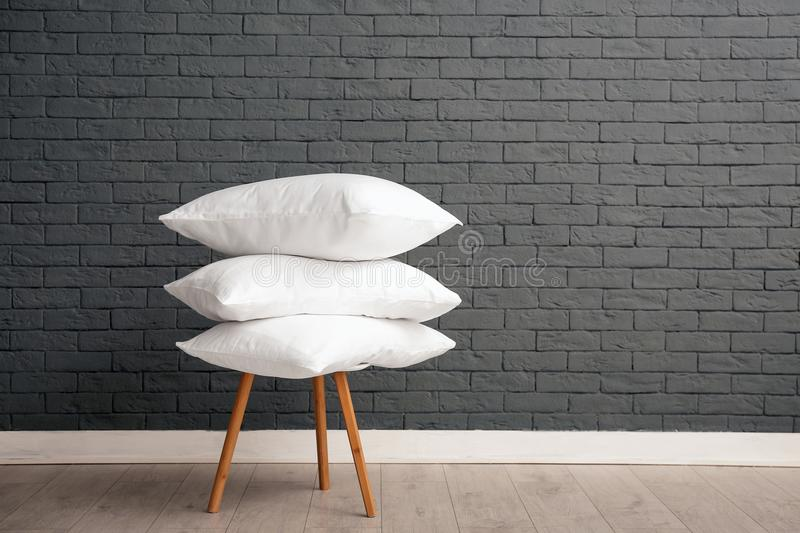Pile of soft bed pillows on chair near brick wall stock images