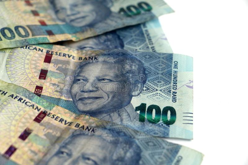 Display of South african currency money hundred rand notes. Pile of South african hundred rand notes money isolated on a white surface with space for text royalty free stock image