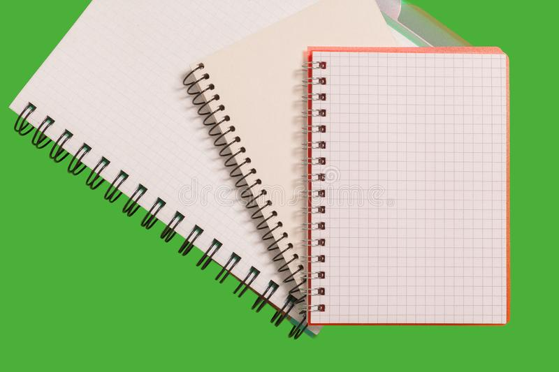 Pile of notebooks. Pile of spiral notebooks lying on a green background. concept of office stationary royalty free stock photo