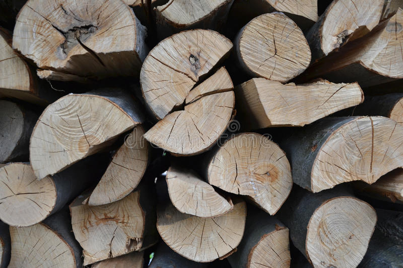 Pile of stacked firewood in rural garden ready for winter. Preparation for the winter. Wooden log abstract background. Dry chopped.  royalty free stock image