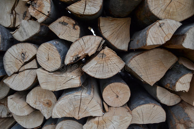 Pile of stacked firewood in rural garden ready for winter. Preparation for the winter. Wooden log abstract background. Dry chopped wood logs royalty free stock photo