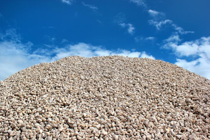 Pile of stones in lime rock quarry against blue sky background.  stock photo