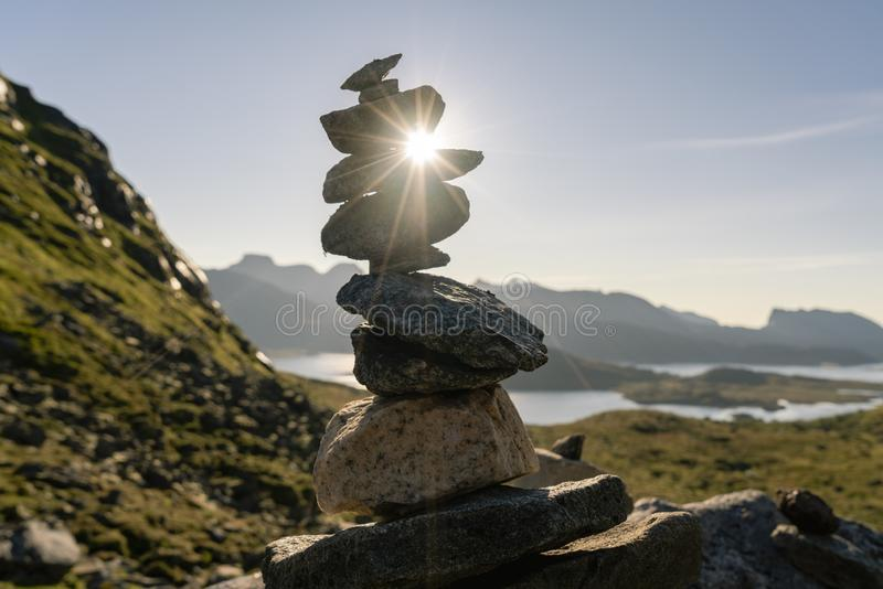 A pile of stones with a ray of sunshine that crosses them in the mountains. royalty free stock photo