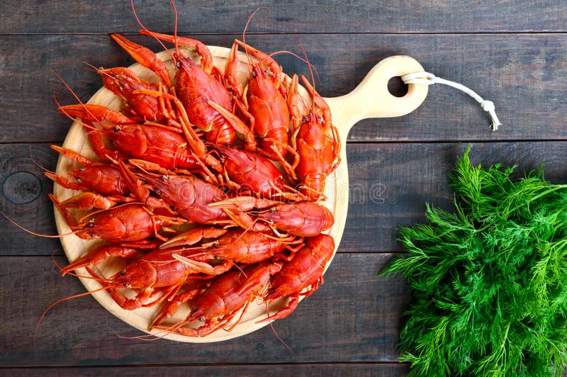 A pile of tasty boiled crawfish on a round wooden tray on a dark table. Top view royalty free stock photo
