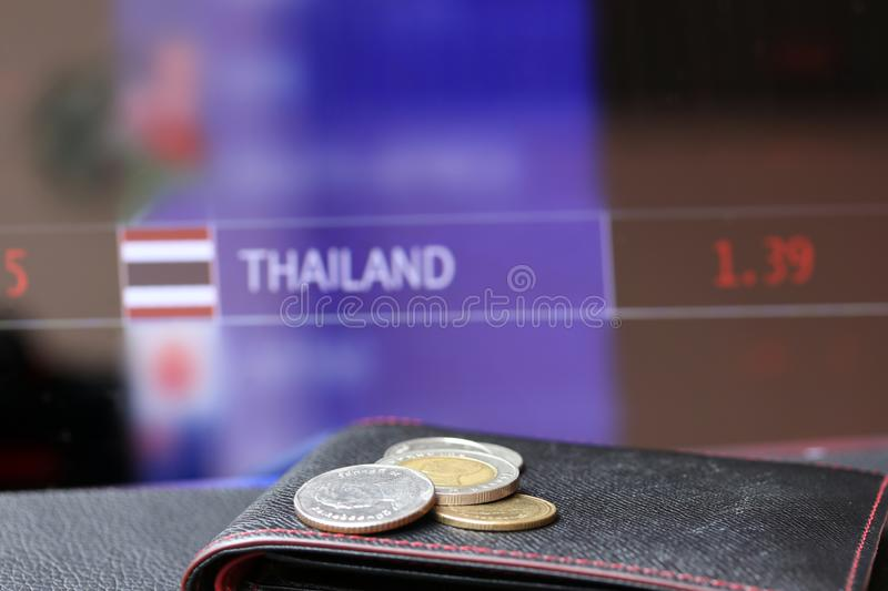 Pile of Thai baht coins on THB on black wallet with black floor and digital board of currency exchange money background. royalty free stock photography