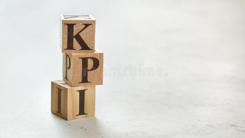 Pile with three wooden cubes - letters KPI meaning Key Performance Indicator on them, space for more text / images at right side.  stock photo
