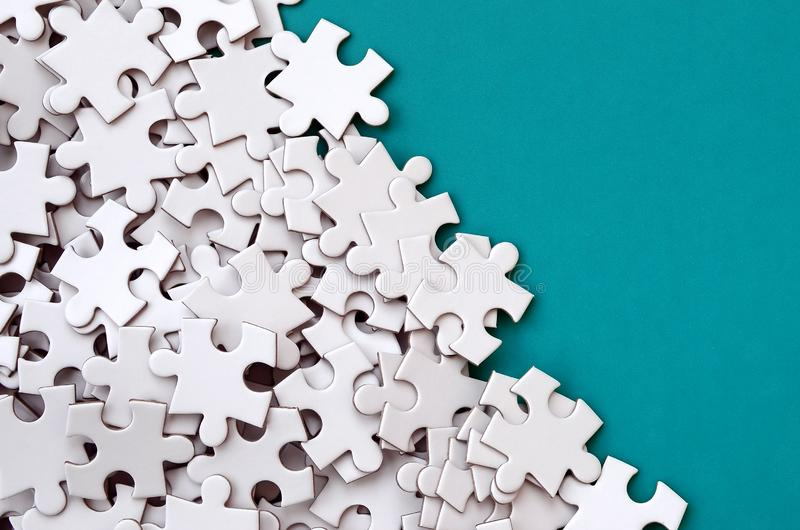 A pile of uncombed elements of a white jigsaw puzzle lies on the background of a blue surface. Texture photo with copy space for. Text royalty free illustration