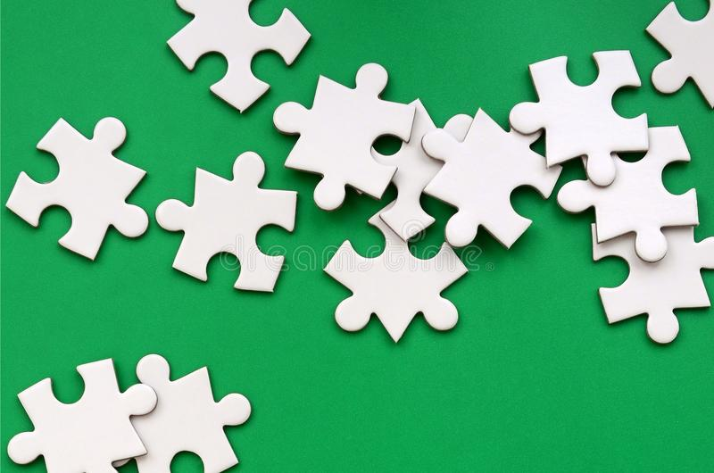 A pile of uncombed elements of a white jigsaw puzzle lies on the background of a green surface. Texture photo with copy space for stock photo