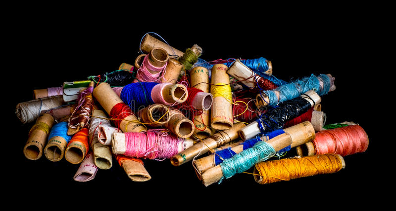 Pile of used colorful spools of thread tailoring. On black background royalty free stock photography