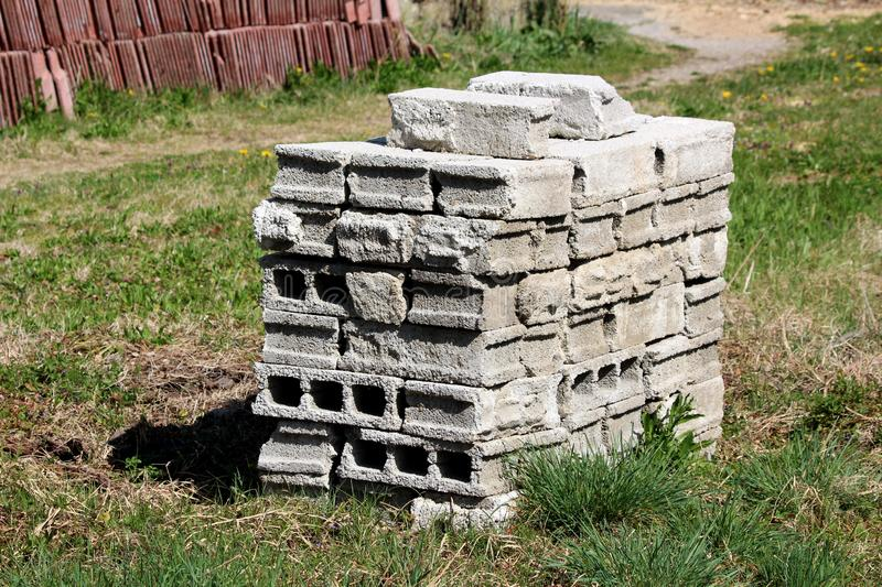 Pile of used grey construction building blocks put in backyard surrounded with uncut grass with roof tiles and small flowers in. Background on warm sunny spring royalty free stock image