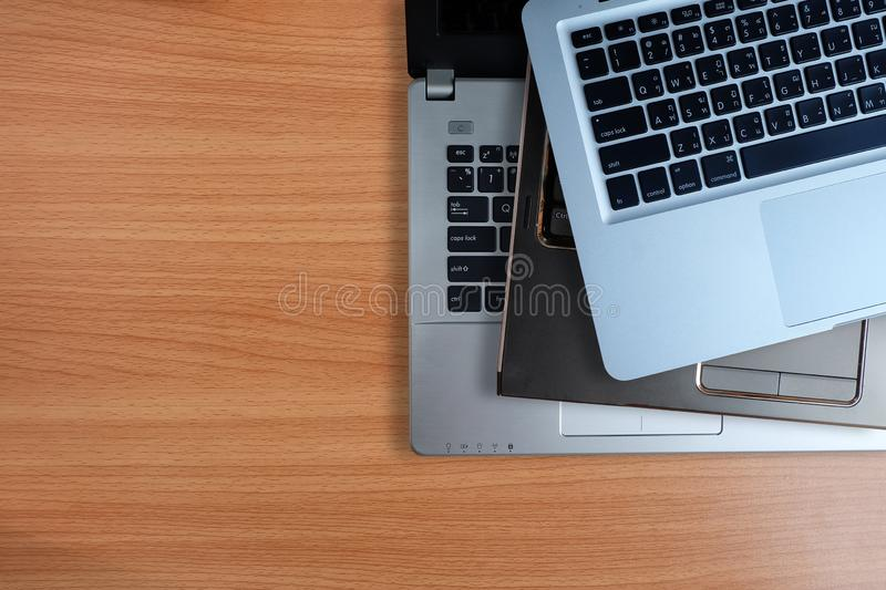 Pile of used laptops computer, on wooden background.Top view copy space royalty free stock photo