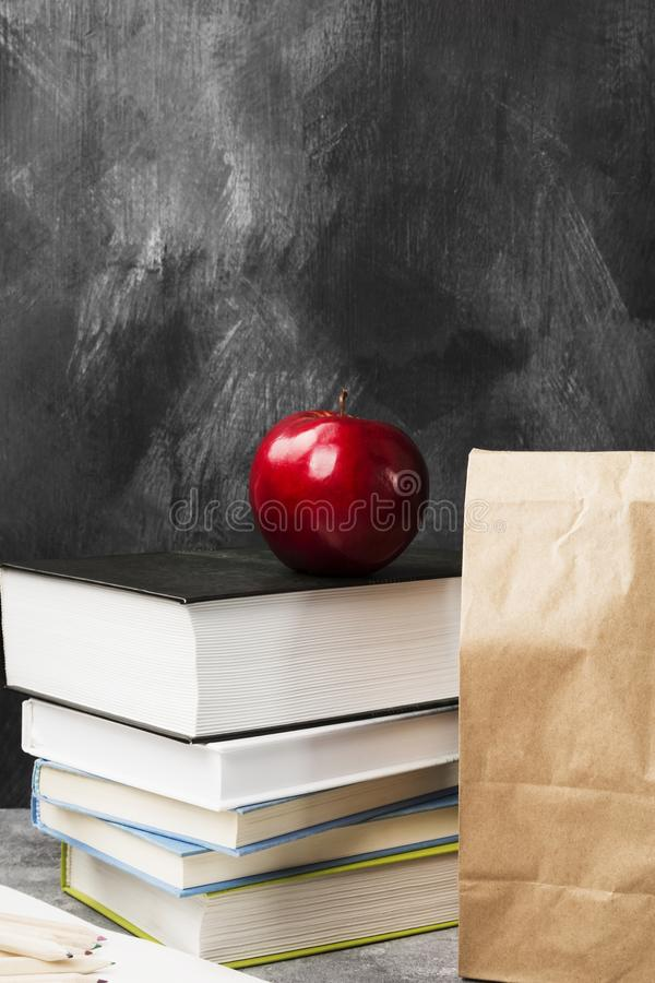Pile of various books, red apple and package of lunch on dark ba stock images