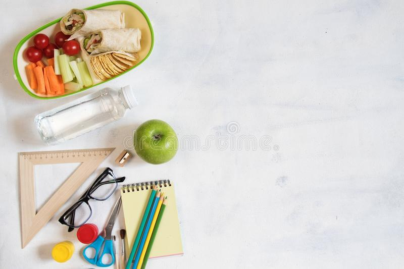 A pile of various stationery on table, notepad, colored pencils, ruler, marker, planer, space for text. Delicious school lunch box royalty free stock photo