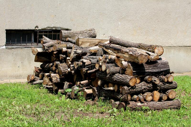 Pile of very old dried stacked firewood prepared for cold winter days in front of dilapidated family house dark grey wall stock photos