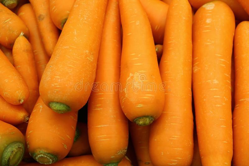 Pile of vibrant orange color fresh carrots selling at the market. Food texture background royalty free stock photos
