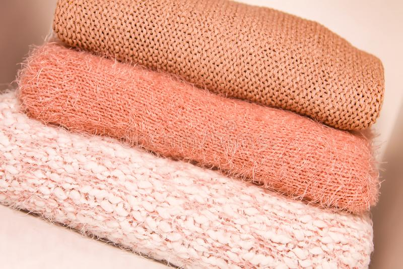 Pile of autumn and winter knitted sweaters on a home wardrobe shelf. Modern fashion clothes in shades of living coral. Pile of warm autumn and winter knitted stock images