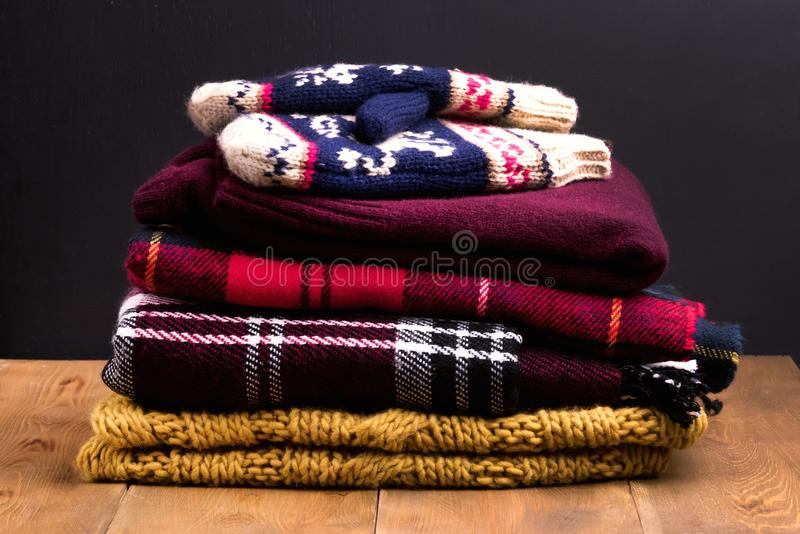 Pile of warm and cozy winter and autumn clothes on wooden background Sweaters cardigans scarf mittens royalty free stock photos