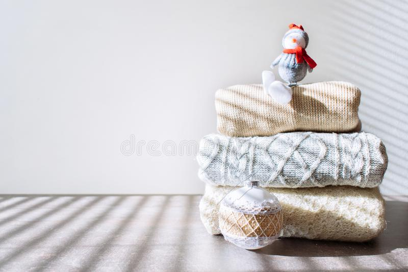 Pile of warm knitted sweaters with Christmas ornament and toy snowman on wooden table on light background stock images