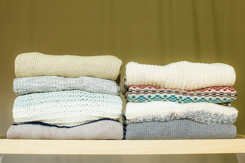 Pile of warm sweaters on a shelf stock images