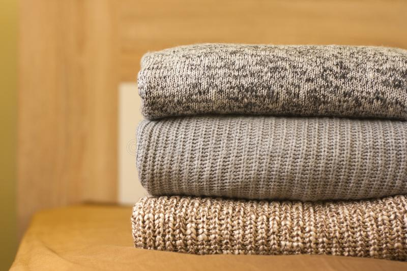 A pile of warm sweaters on the wood bed. A pile of knitted sweaters on the wood bed. Warm comfortable clothes stock images