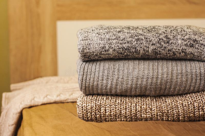A pile of warm winter autumn sweaters on the wood bed. A pile of knitted winter or autumn sweaters on the wood bed. Warm comfortable clothes stock photo