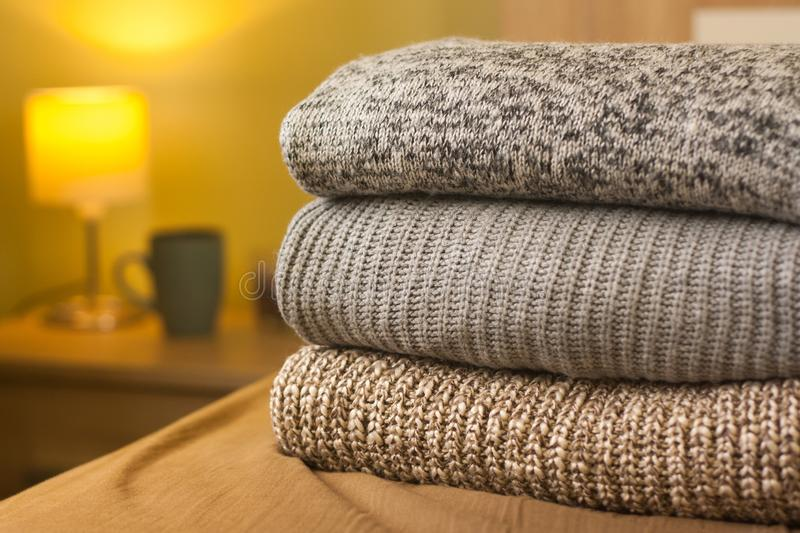 A pile of warm winter autumn sweaters on the wood bed in room. A pile of knitted winter or autumn sweaters on the wood bed. Lamp and cup in background. Warm stock photography