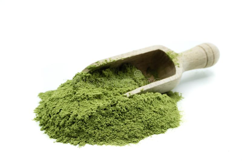 Pile of wheatgrass powder with wooden scoop on white background. NPile of wheatgrass powder with wooden scoop white background royalty free stock photography