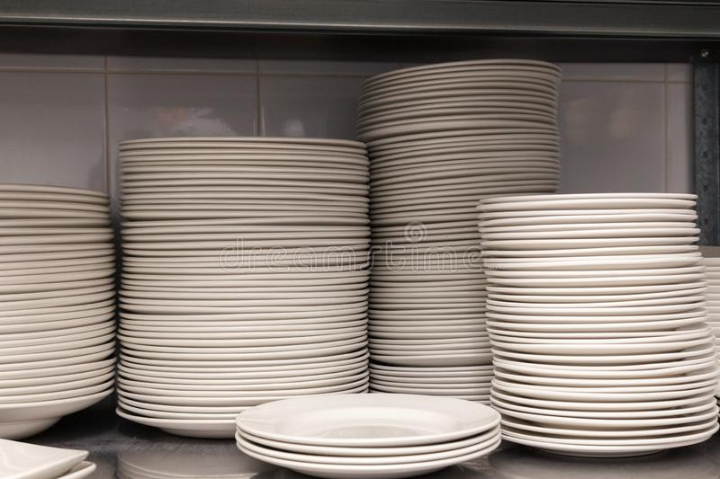 A pile of white clean ceramic porcelain plates on a metal rack in the back of the restaurant. Concept of preparation for banquet,. Pile of white clean ceramic stock image