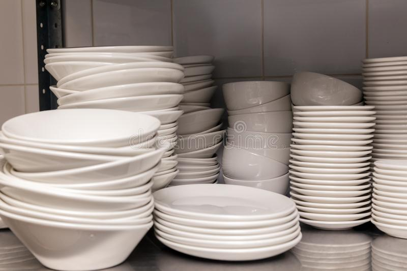 A pile of white clean ceramic porcelain plates on a metal rack in the back of the restaurant. Concept of preparation for banquet,. Pile of white clean ceramic stock images