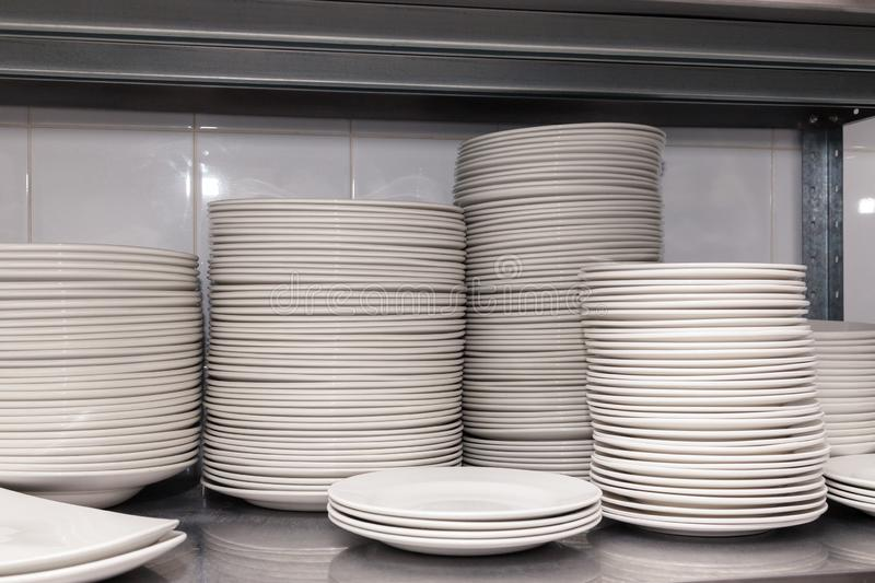 A pile of white clean ceramic porcelain plates on a metal rack in the back of the restaurant. Concept of preparation for banquet,. Pile of white clean ceramic royalty free stock photo