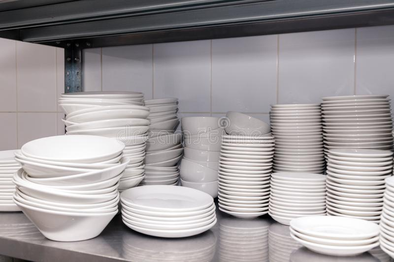 A pile of white clean ceramic porcelain plates on a metal rack in the back of the restaurant. Concept of preparation for banquet,. Pile of white clean ceramic royalty free stock photos