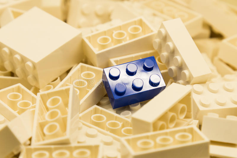 Pile of white color building blocks with selective focus and highlight on one particular blue block using available light.  royalty free stock photography