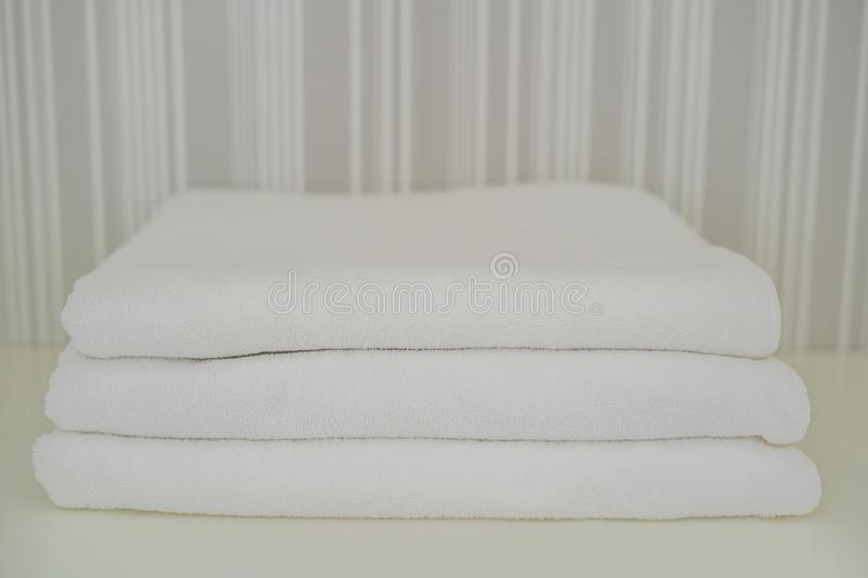 A pile of white fluffy towels in the closet. Service in the hotel concept. laundry royalty free stock image