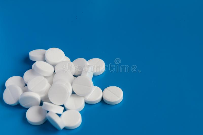 Pile of white medical pills lies on a blue background. pharmaceutical concept royalty free stock photos