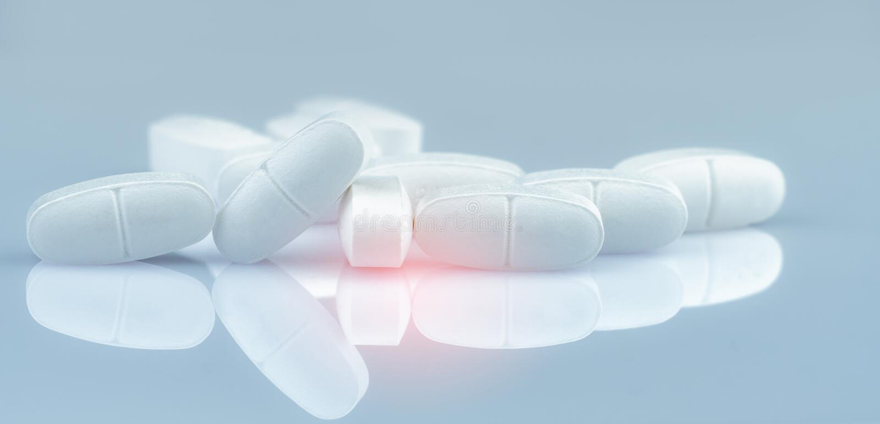 Pile of white oblong tablets pills on gradient background. White antibiotic tablet pills. Pharmaceutical industry. Pharmacy stock images
