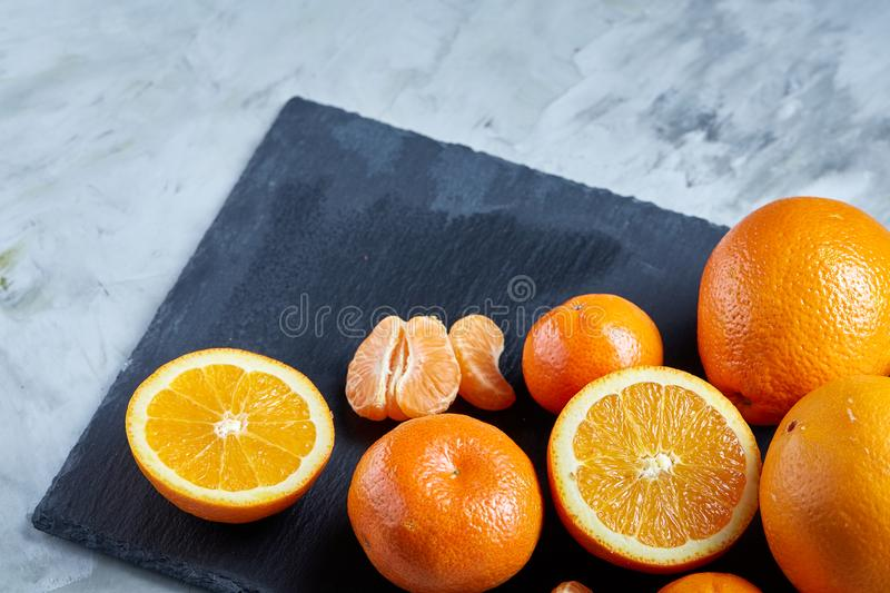 Pile of whole and half cut fresh tangerine and orange on cutting board, close-up royalty free stock images