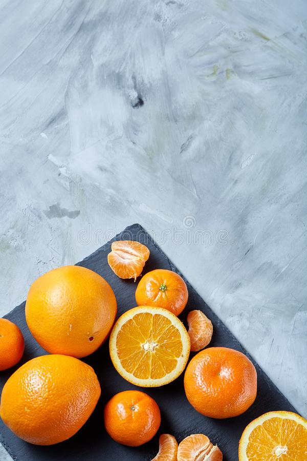 Pile of whole and half cut fresh tangerine and orange on cutting board, close-up royalty free stock photos