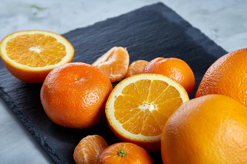 Pile of whole and half cut fresh tangerine and orange on cutting board, close-up royalty free stock image
