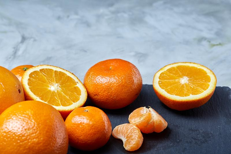 Pile of whole and half cut fresh tangerine and orange on cutting board, close-up stock photo