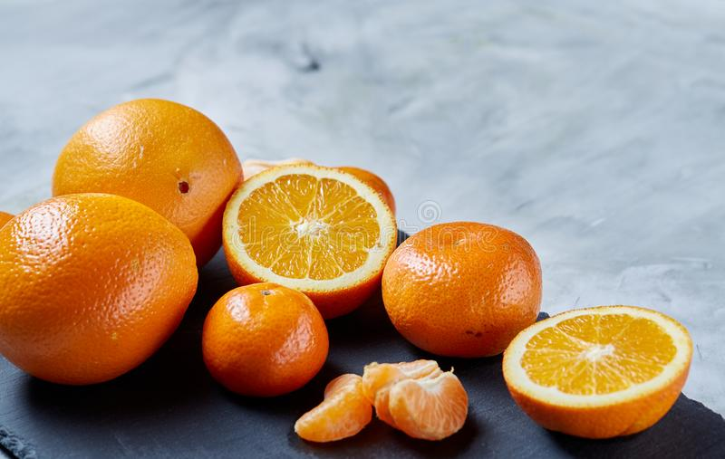Pile of whole and half cut fresh tangerine and orange on cutting board, close-up royalty free stock photo