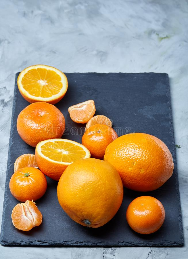 Pile of whole and half cut fresh tangerine and orange on cutting board, close-up stock photography