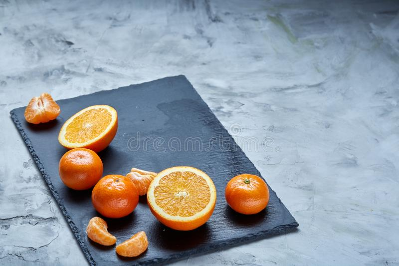 Pile of whole and half cut fresh tangerine and orange on cutting board, close-up stock images