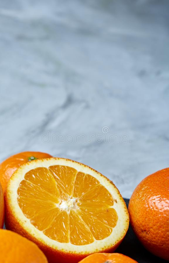 Pile of whole and half cut fresh tangerine and orange on cutting board, close-up stock photos