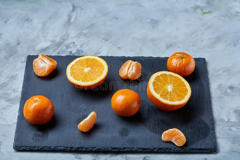 Pile of whole and half cut fresh tangerine and orange on cutting board, close-up stock image