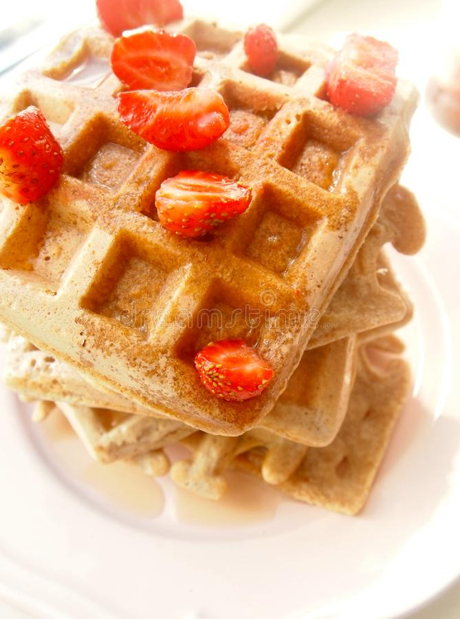 A pile of whole wheat waffles with strawberries and maple syrup stock photos